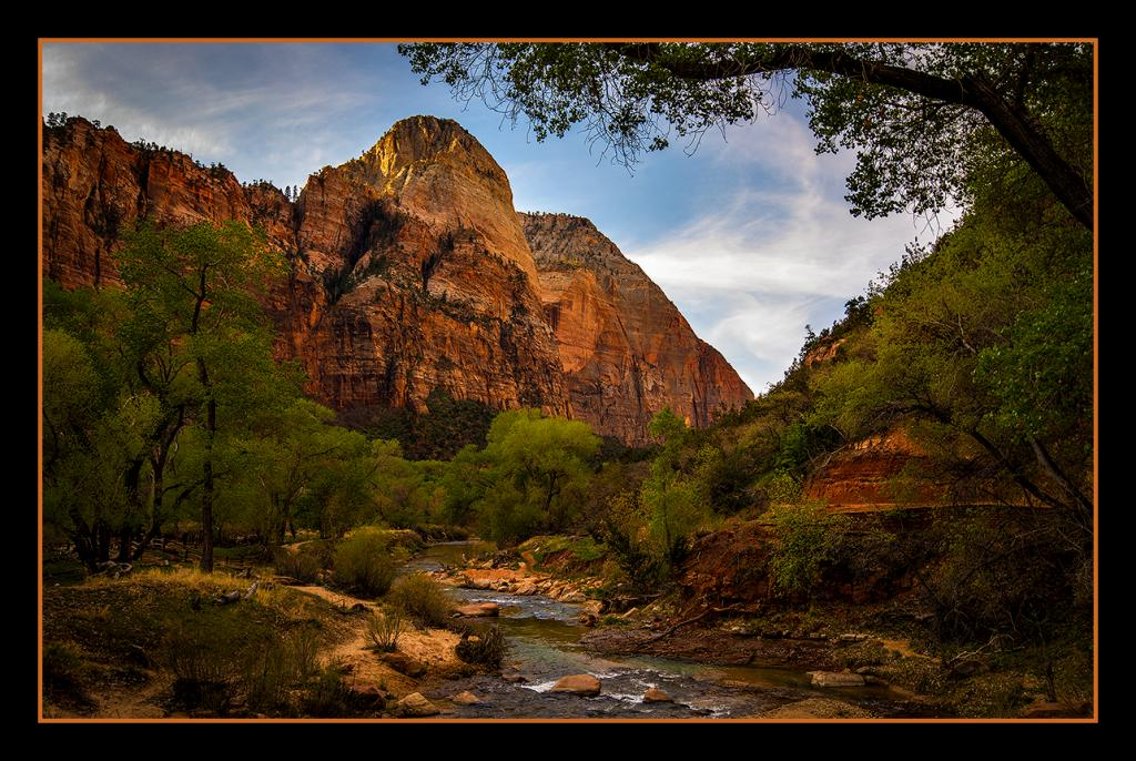 Morning sun begins to bathe ancient red rock and fresh Spring green.<br />Zion National Park, Utah, USA.   April 2014