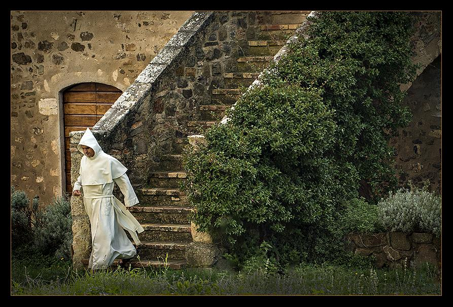 Rushing to one of the seven daily prayers, this monk from the 'Canons Regular' (priests living in community under the Rule of St. Augustine and sharing their property in common) prepares to enter the Abbey of Sant'Antimo and join his brothers in hauntingly beautiful Gregorian Chant.