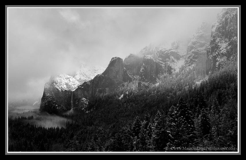 "The Yosemite snow of January 19-22 brought marvelous and varied conditions of all descriptions. Here, on the afternoon of the 19th, the storm was getting underway in earnest before breaking for a period and revealing Bridal Veil Fall and Cathedral Rocks that had, moments before, been shrouded in cloud.Many elements work together to make this a pleasing image for me. The leading lines of granite and trees bring the eye from top right down to the fall in lower left. The valley mist suggests that it is not mist at all but rather a pool of water emanating from the output of Bridal Veil fall.The ""normal"" view from this position at Tunnel View usually includes El Capitan on the left, making for a fairly static depiction. Here, I wanted to emphasize the sweeping grandeur of the place by aiming for a more dynamic, sweeping flow of the scene."